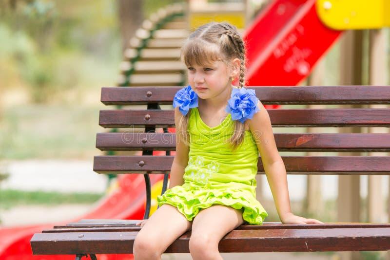 Retrato de la muchacha de cinco años del trastorno que se está sentando en el banco en el fondo del patio imagenes de archivo