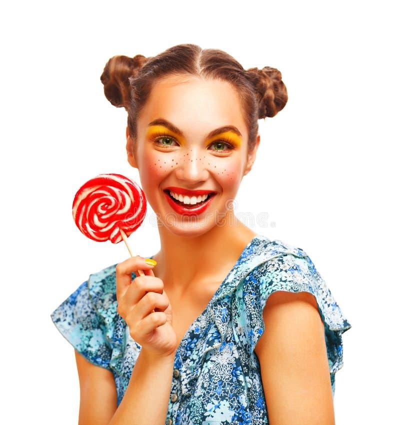 Retrato de la muchacha de la belleza que sostiene la piruleta colorida imagen de archivo libre de regalías
