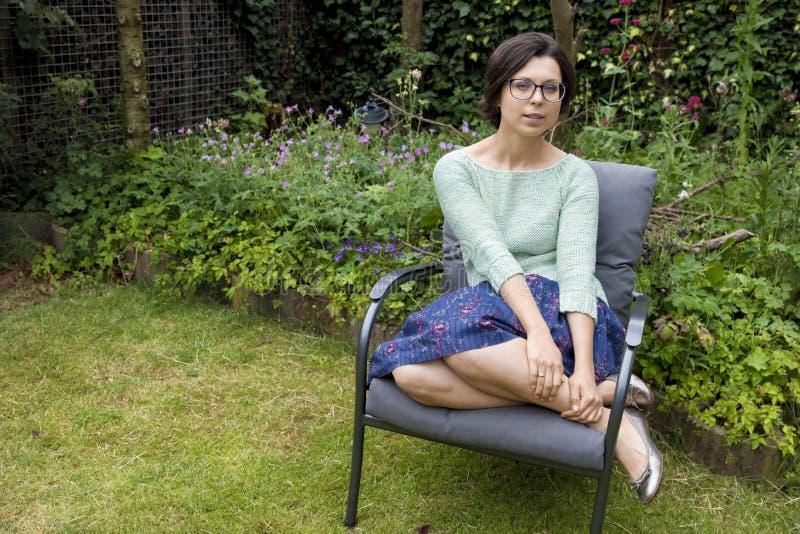 Retrato de la muchacha de moda en los vidrios que se sientan en silla en patio trasero fotografía de archivo libre de regalías
