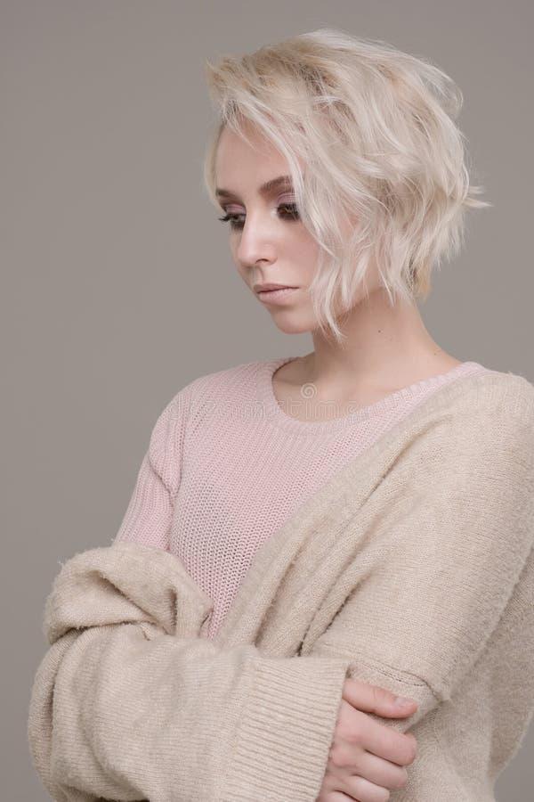 Retrato de la muchacha del blonde con maquillaje del ojo oscuro y del pelo corto en un pálido - jersey rosado y suéter de gran ta foto de archivo