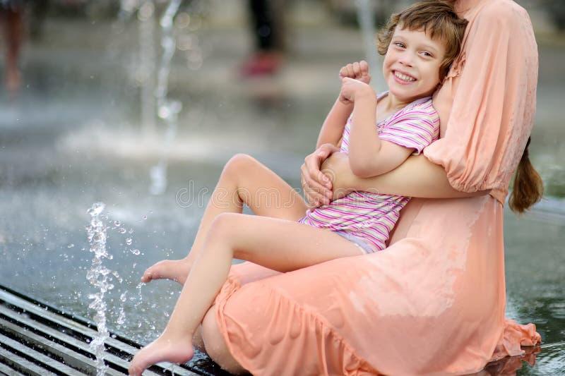 Retrato de la muchacha discapacitada hermosa en los brazos de su madre que se divierte en fuente del parque público en el día de  foto de archivo