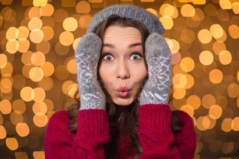 Retrato de la muchacha divertida sorprendida en sombrero y manoplas hechos punto imágenes de archivo libres de regalías