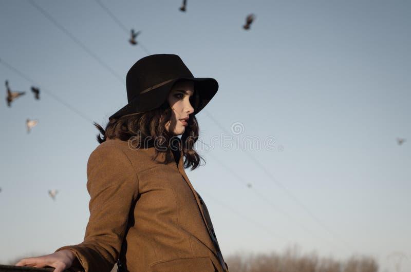 Retrato de la muchacha elegante triste al aire libre con las palomas en el cielo del otoño imagenes de archivo