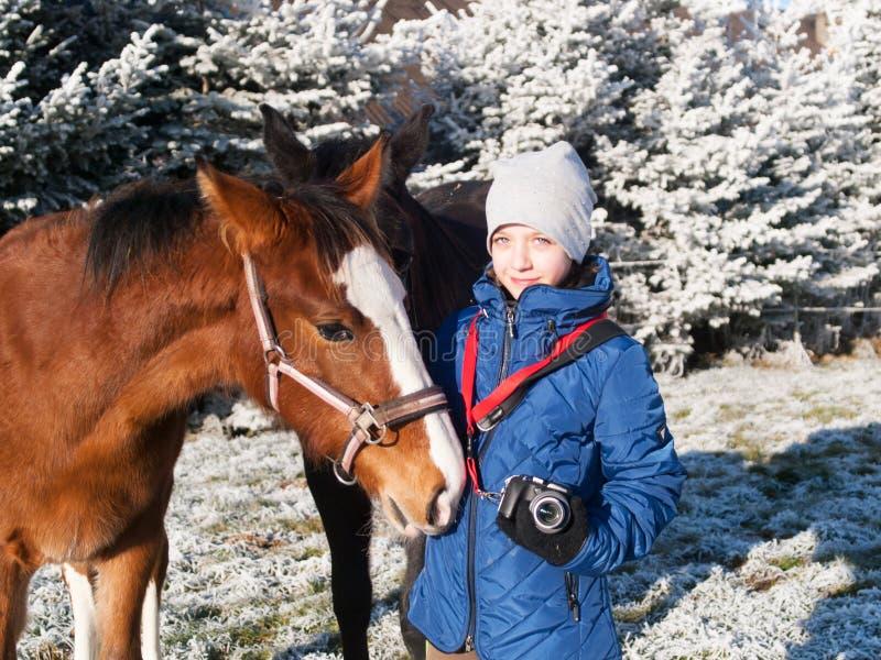 Retrato de la muchacha en chaqueta azul con los potros en pasto escarchado imagen de archivo libre de regalías
