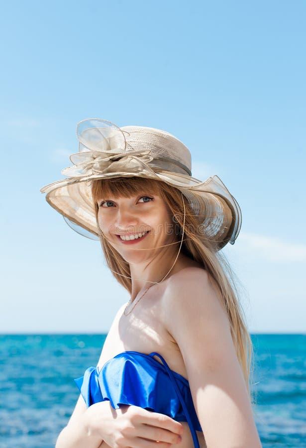 Retrato de la muchacha en top del traje de baño y sombrero azules del amplio-borde imágenes de archivo libres de regalías