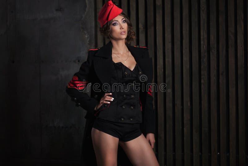 Retrato de la muchacha en un uniforme negro del aviador con el sombrero imágenes de archivo libres de regalías