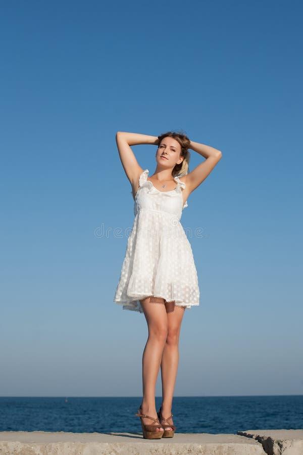 Retrato de la muchacha en vestido sin mangas blanco corto imagenes de archivo