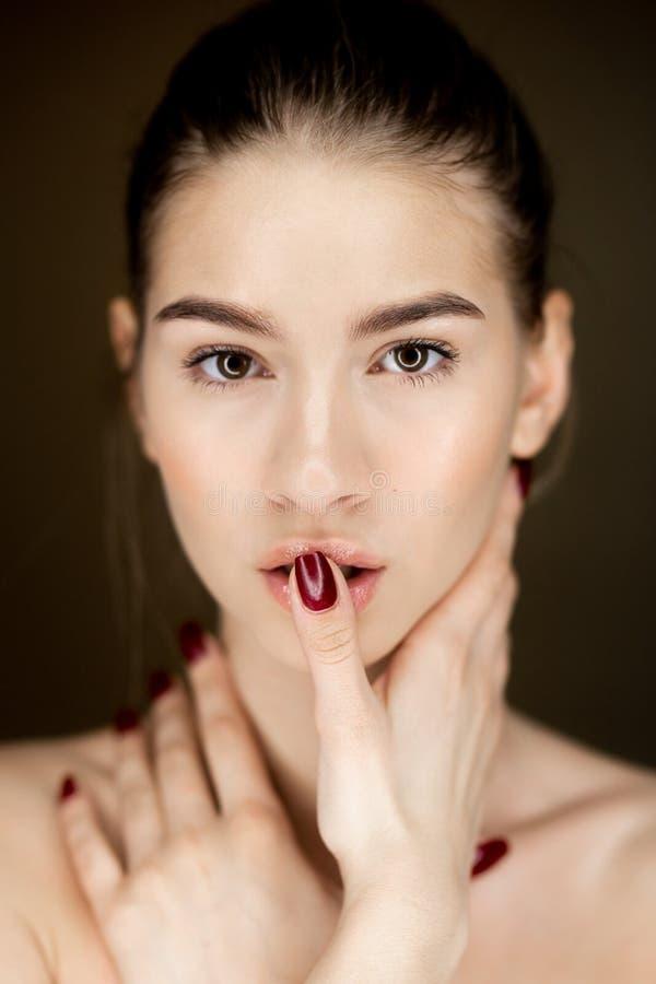 Retrato de la muchacha encantadora joven con el maquillaje natural que lleva a cabo sus manos en su cara fotos de archivo libres de regalías