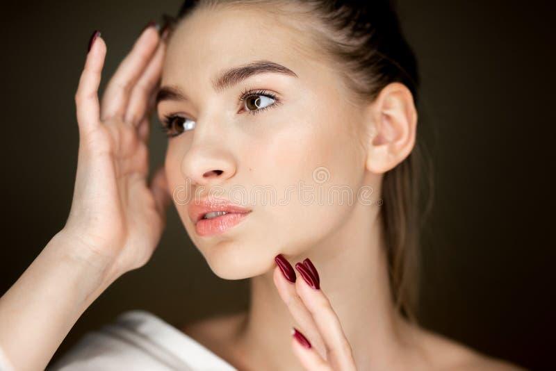 Retrato de la muchacha encantadora joven con el maquillaje natural que lleva a cabo sus manos en su cara fotografía de archivo