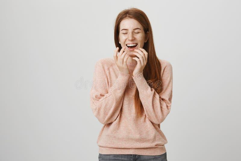 Retrato de la muchacha europea feliz emotiva del jengibre que ríe hacia fuera ruidosamente con los ojos cerrados, cubriendo la bo imagen de archivo