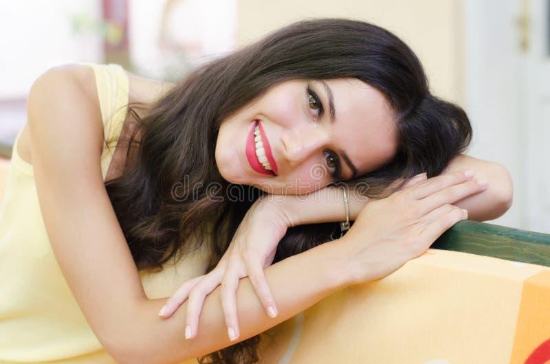 Retrato de la muchacha feliz hermosa con el pelo largo que se sienta solamente adentro foto de archivo libre de regalías