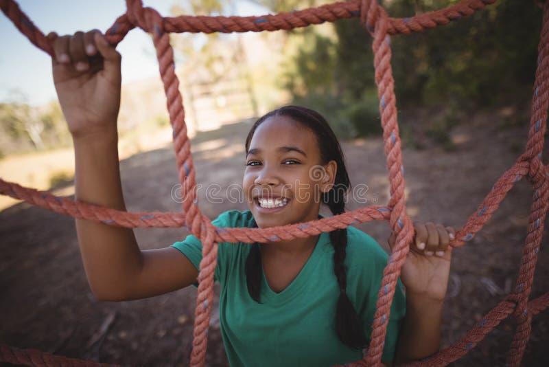 Retrato de la muchacha feliz que coloca la red cercana durante carrera de obstáculos foto de archivo