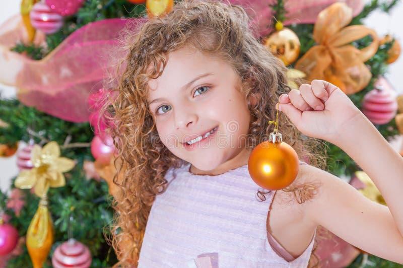 Retrato de la muchacha feliz que sostiene una bola de la Navidad delante de un árbol de navidad, concepto de la Navidad foto de archivo libre de regalías