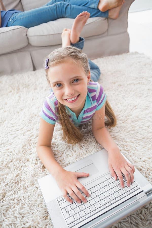 Retrato de la muchacha feliz que usa el ordenador portátil mientras que miente en la manta fotografía de archivo