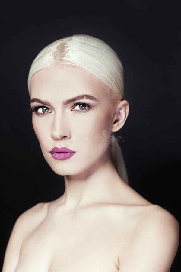 Retrato de la muchacha hermosa con cierre del pelo rubio para arriba aislada en fondo negro imagen de archivo
