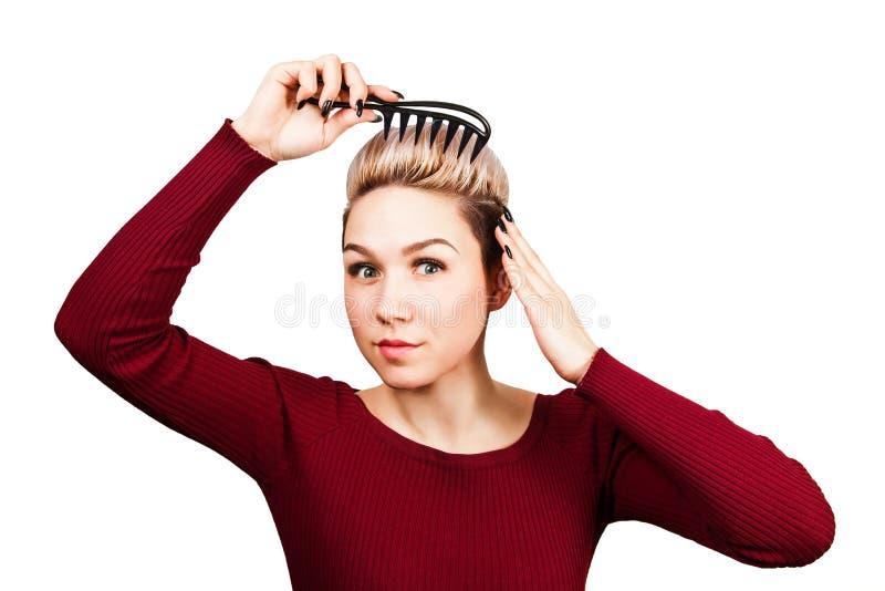 Retrato de la muchacha hermosa con el peine corto nad de la tenencia del peinado que peina el pelo Aislado en el fondo blanco imagen de archivo libre de regalías