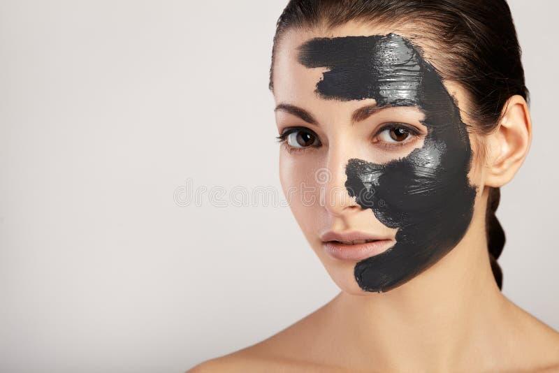 Retrato de la muchacha hermosa con la arcilla negra de la máscara fotografía de archivo libre de regalías