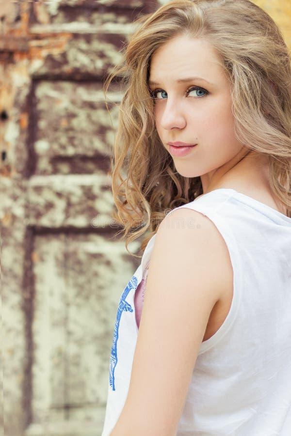 Retrato de la muchacha hermosa con los labios llenos en una camiseta blanca que se coloca en la calle cerca del edificio viejo fotografía de archivo