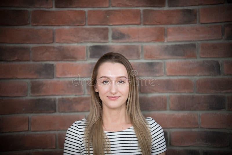 Retrato de la muchacha hermosa joven con el pelo largo en fondo de la pared de ladrillo fotos de archivo