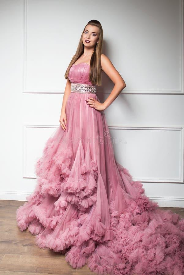 Retrato de la muchacha hermosa joven en vestido rosado largo foto de archivo