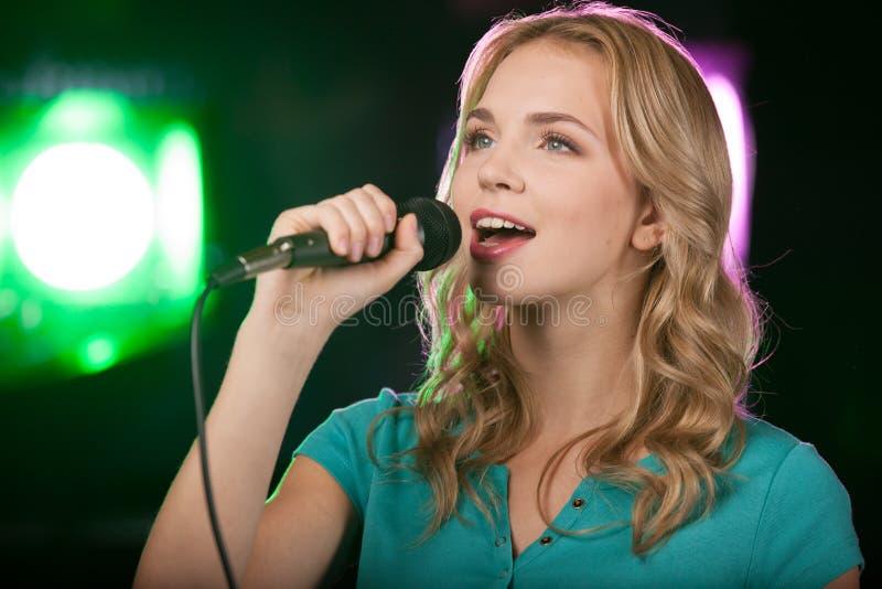 Retrato de la muchacha hermosa joven que canta imagenes de archivo