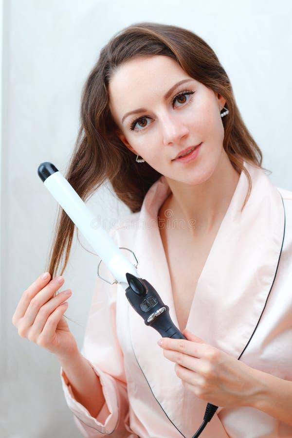 Retrato de la muchacha hermosa joven que hace el peinado en casa foto de archivo