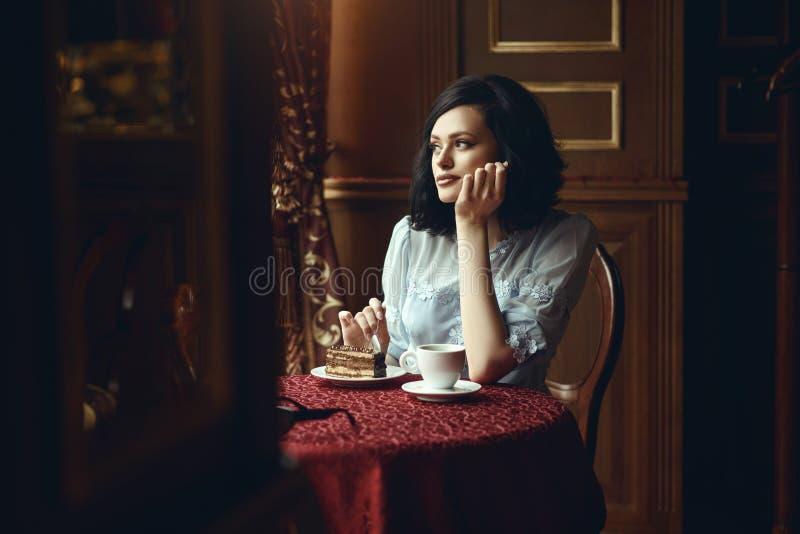 Retrato de la muchacha hermosa joven que se sienta en la tabla en la cafetería acogedora y que mira la ventana cuidadosamente, su imágenes de archivo libres de regalías