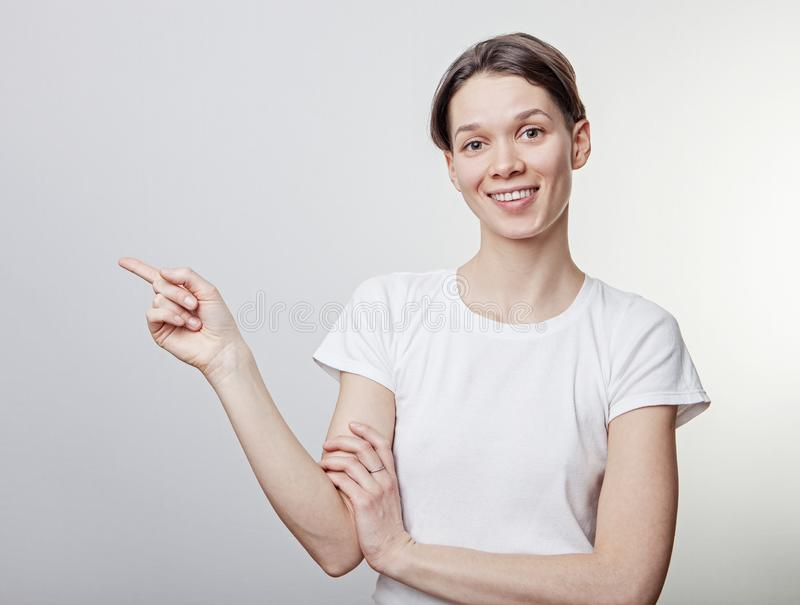 Retrato de la muchacha hermosa, mirando la cámara y señalando en espacio de la copia Aislado contra la pared gris en blanco del e imagen de archivo