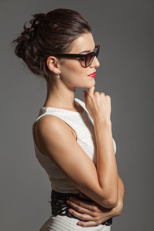 Retrato de la muchacha hermosa morena que presenta en el vestido blanco imagen de archivo