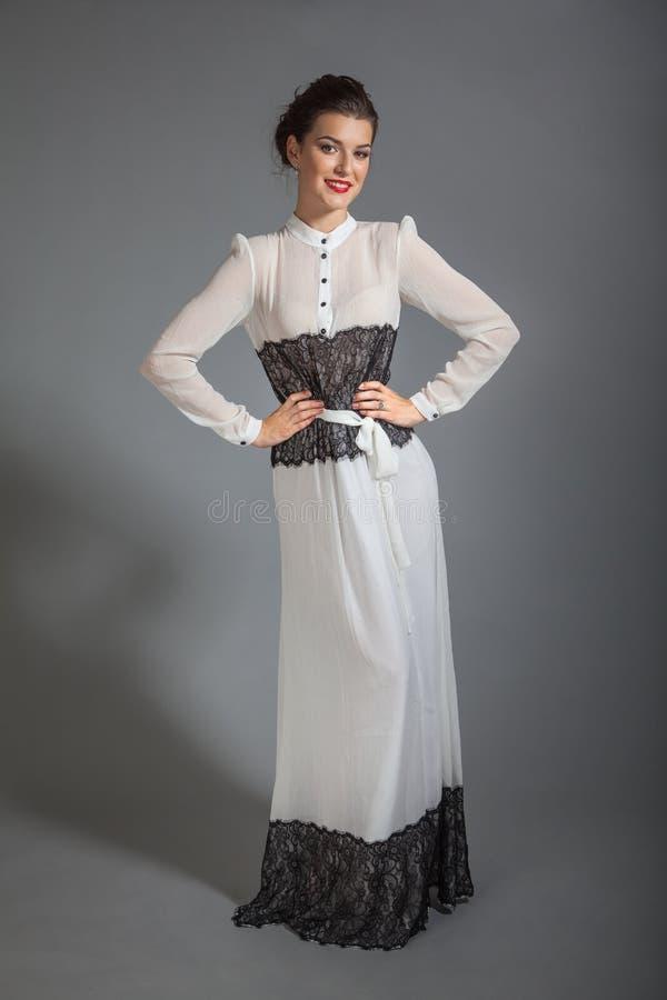 Retrato de la muchacha hermosa morena que presenta en vestido del retrostyle foto de archivo