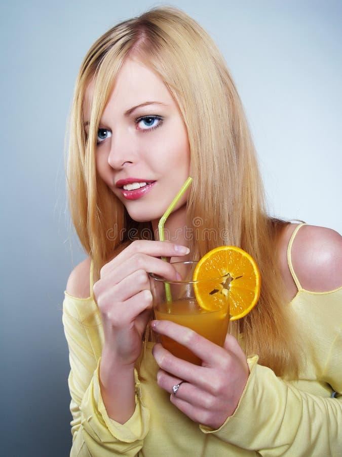 Retrato de la muchacha hermosa que bebe el zumo de naranja fotografía de archivo libre de regalías