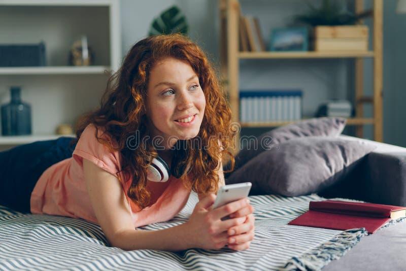 Retrato de la muchacha hermosa que miente en el sofá en casa que celebra la sonrisa del smartphone fotografía de archivo