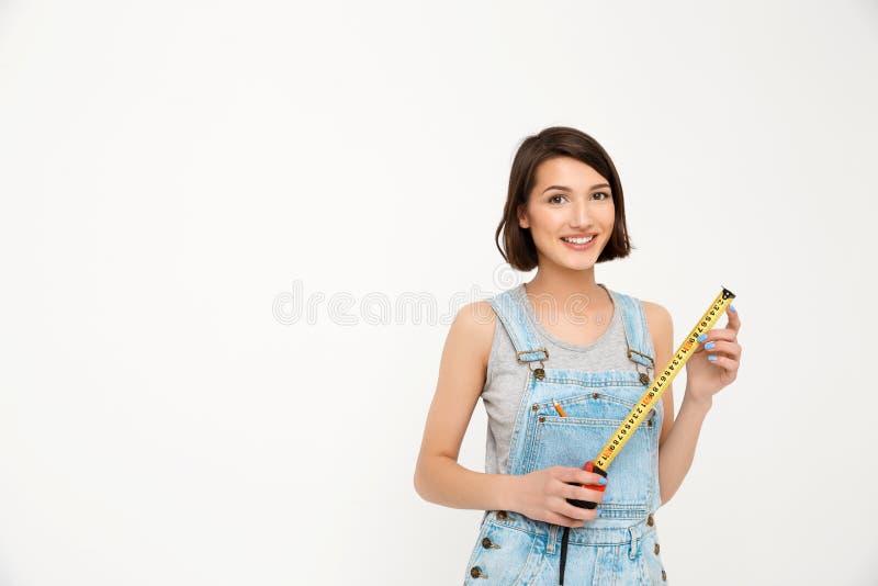 Retrato de la muchacha hermosa sonriente de los jóvenes, llevando a cabo cinta métrica imagen de archivo