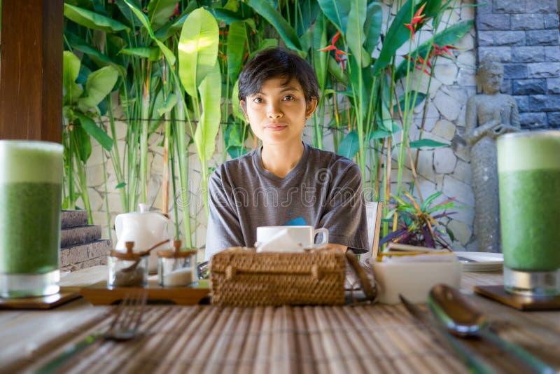 Retrato de la muchacha indonesia asiática linda de la belleza de la forma de vida que espera su desayuno fotografía de archivo