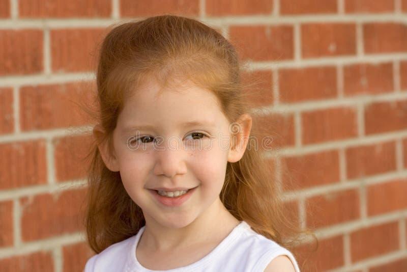Retrato de la muchacha joven del cabrito del redhead por la pared de ladrillo imágenes de archivo libres de regalías