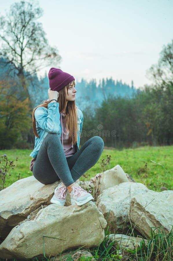 Retrato de la muchacha joven del inconformista que disfruta de una vista asombrosa de montañas, viajero bastante femenino, sentán foto de archivo
