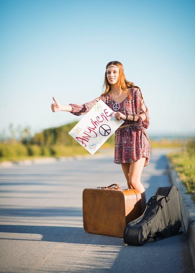Retrato de la muchacha joven preciosa del hippie que hace autostop en un camino fotos de archivo libres de regalías