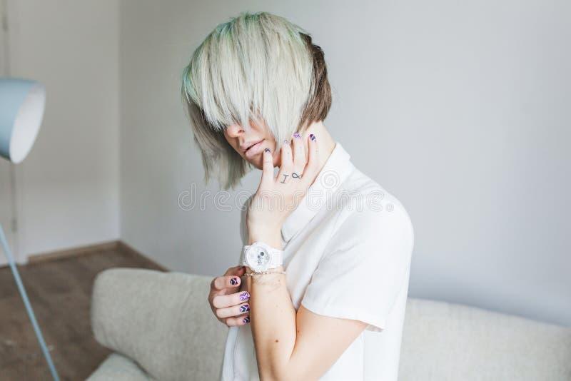 Retrato de la muchacha linda con el peinado corto gris que se sienta en el sofá en estudio Ella lleva el vestido blanco Su cubier imagen de archivo libre de regalías