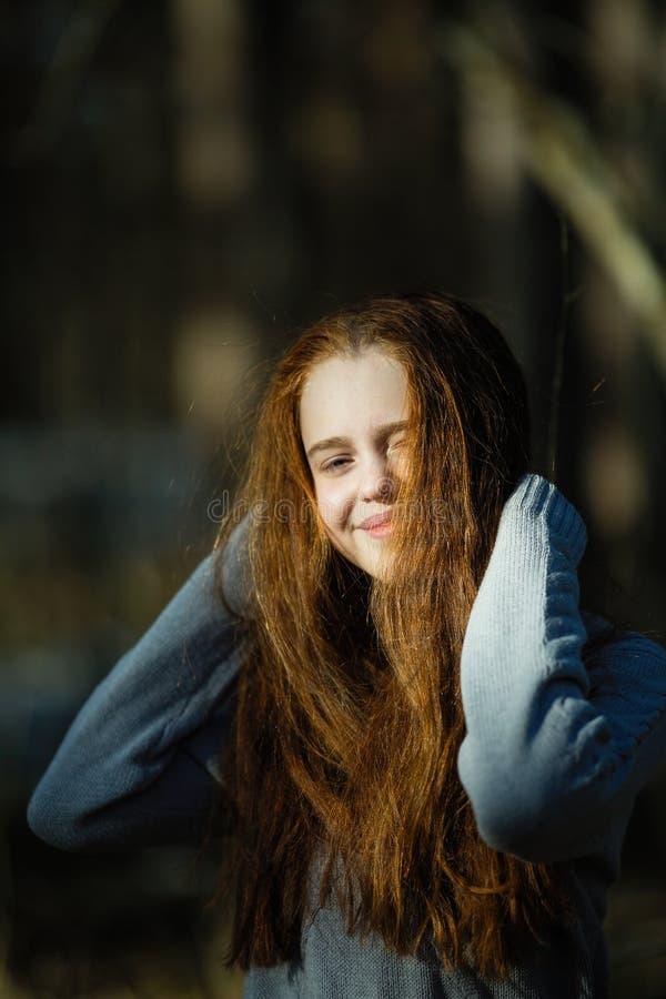 Retrato de la muchacha linda de doce años con el pelo rojo ardiente que presenta en el parque del pino fotografía de archivo