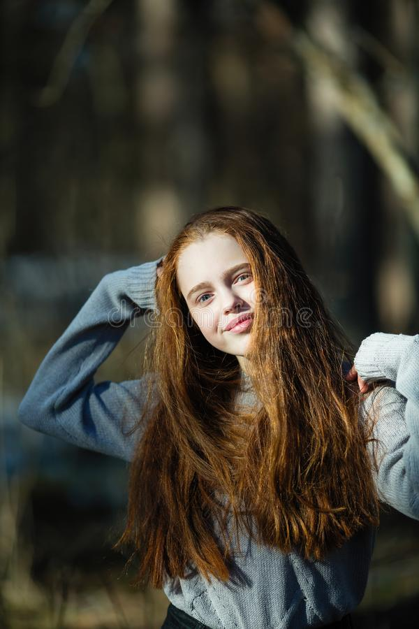 Retrato de la muchacha linda de doce a?os con el pelo rojo ardiente que presenta en el parque del pino foto de archivo