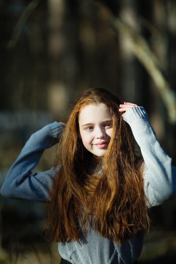Retrato de la muchacha linda de doce a?os con el pelo rojo ardiente que presenta en el parque del pino imagenes de archivo
