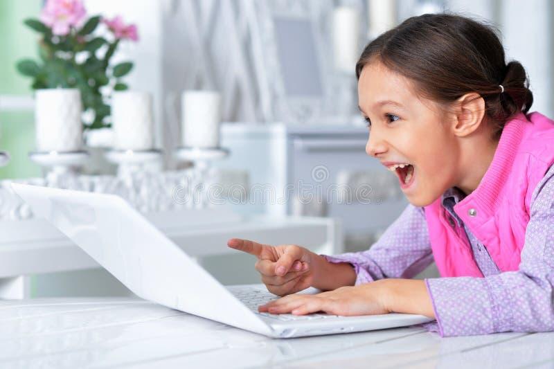Retrato de la muchacha linda emocional que usa el ordenador port?til imagenes de archivo