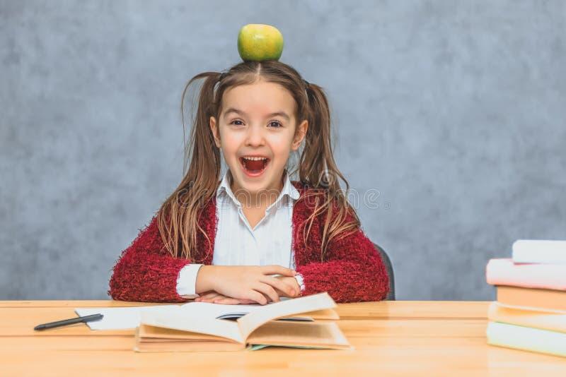 Retrato de la muchacha lista linda con la manzana en su cabeza Sentándose de una pila de libros en la tabla, una copia del espaci imagenes de archivo
