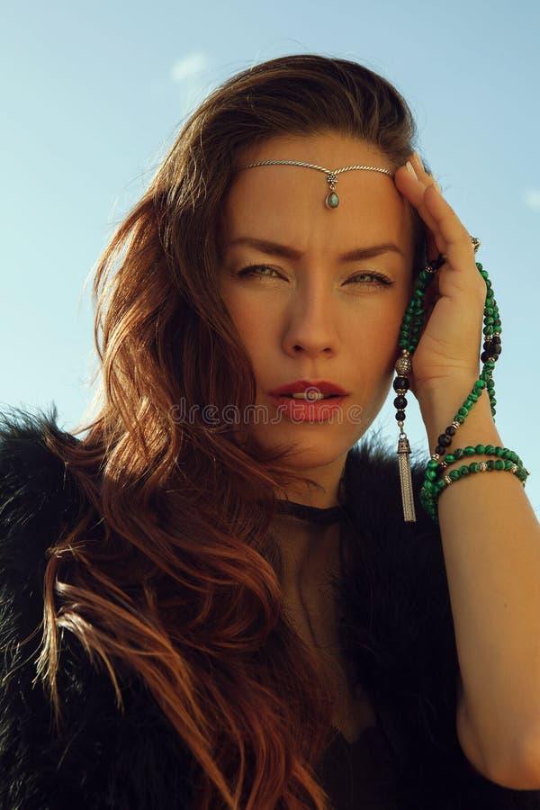 Retrato de la muchacha de moda en vestido negro y de la tiara stilish con jewellry verde en su mano en luz del sol en fondo del c foto de archivo