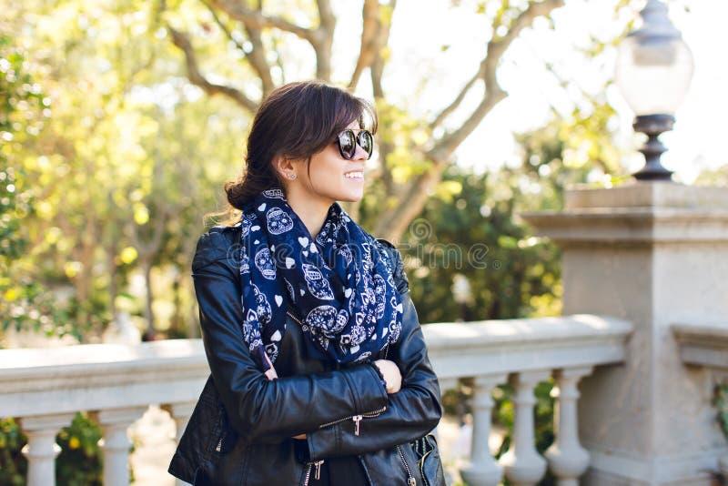 Retrato de la muchacha morena bonita en gafas de sol que sonríe para echar a un lado en parque Ella lleva la chaqueta negra y el  imagenes de archivo