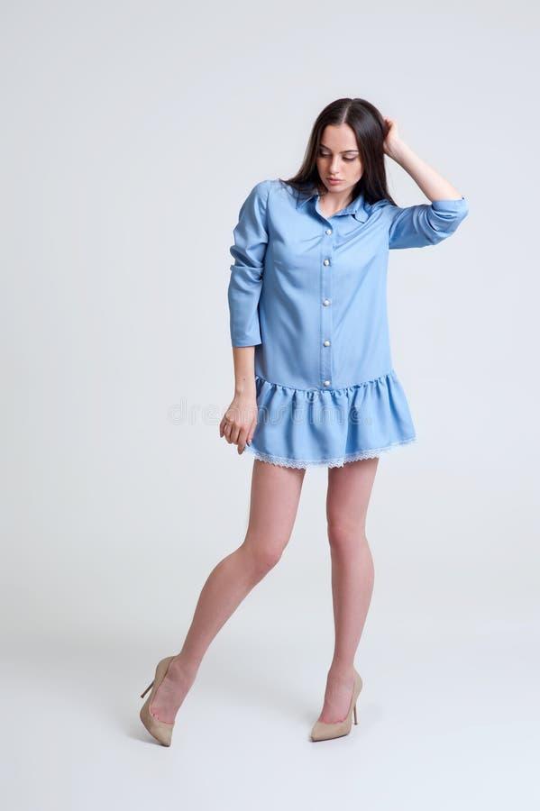 Retrato de la muchacha morena hermosa en vestido azul corto foto de archivo