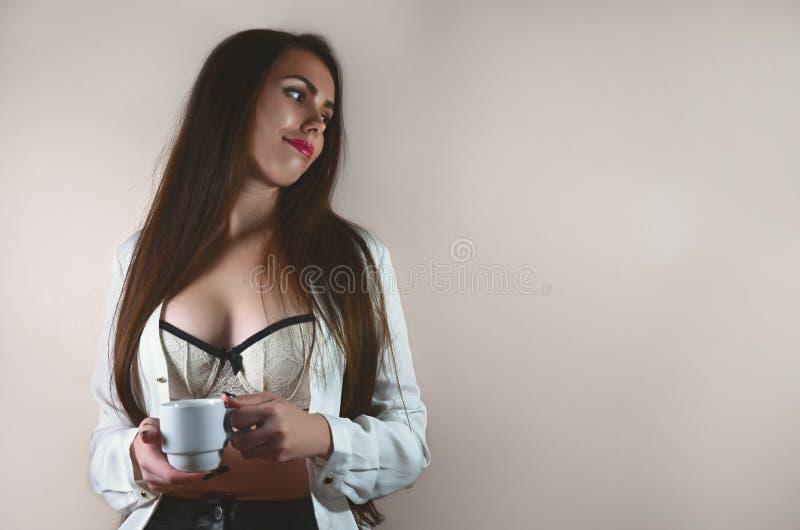 Retrato de la muchacha morena joven y caucásica en una camisa blanca y una ropa interior blanca con la taza blanca imagen de archivo