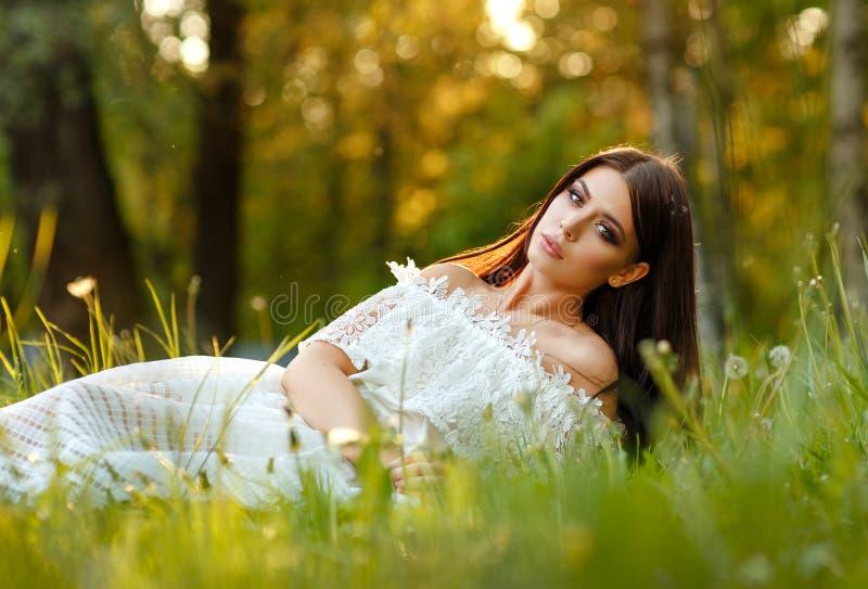 Retrato de la muchacha morena sensual hermosa en el sitti blanco del vestido foto de archivo libre de regalías
