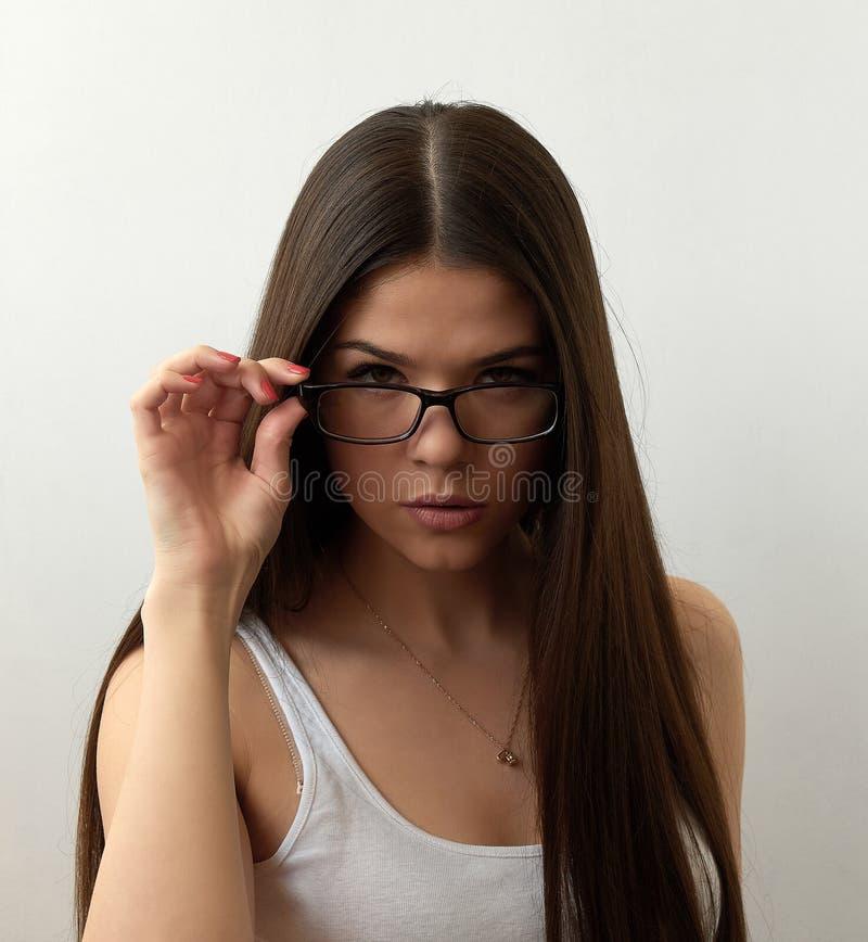 Retrato de la muchacha morena seria que toca sus gafas elegantes Las lentes que llevaban modelo de la mujer atractiva joven que m fotografía de archivo libre de regalías