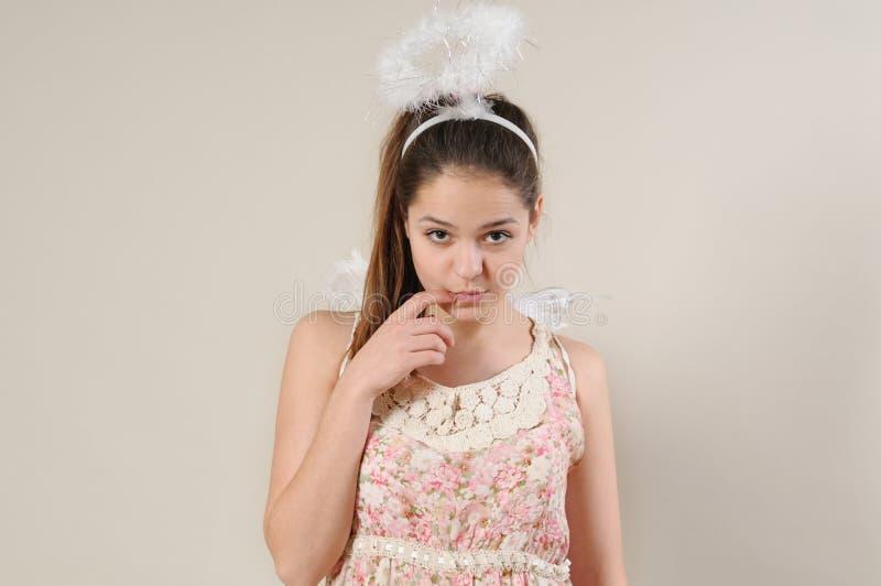 Retrato de la muchacha muy tímida linda del ángel con el finger cerca de su boca fotografía de archivo libre de regalías